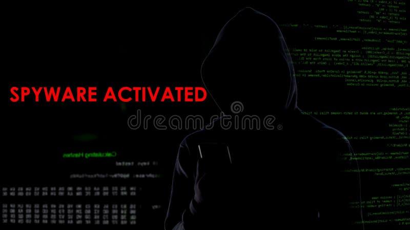 Spyware de déclenchement de pirate informatique masculin sur le smartphone, collectant des informations privées photographie stock libre de droits