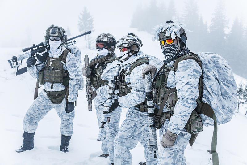 Squad of soldiers in winter forest. Winter arctic mountains warfare. Action in cold conditions. Squad of soldiers with weapons in forest somewhere above the stock images