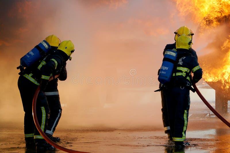 Squadra antincendi che combatte grande fuoco fotografia stock libera da diritti