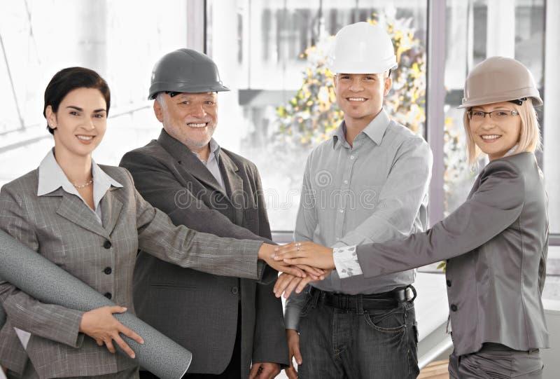 Squadra dell'architetto in mani della holding dell'ufficio nell'unità immagini stock libere da diritti