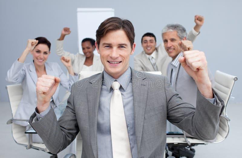 Squadra di affari che celebra un successo con le mani in su fotografie stock