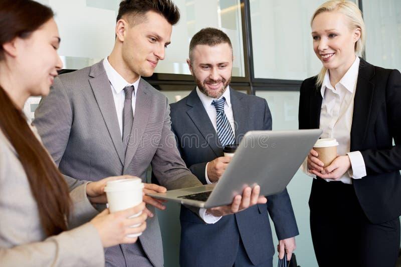 Squadra di affari che per mezzo del computer portatile immagine stock libera da diritti