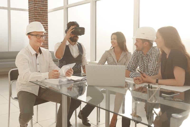 Squadra di giovani progettisti professionisti che discutono le idee circa il modello durante il tavolo di riunione nello studio m immagini stock