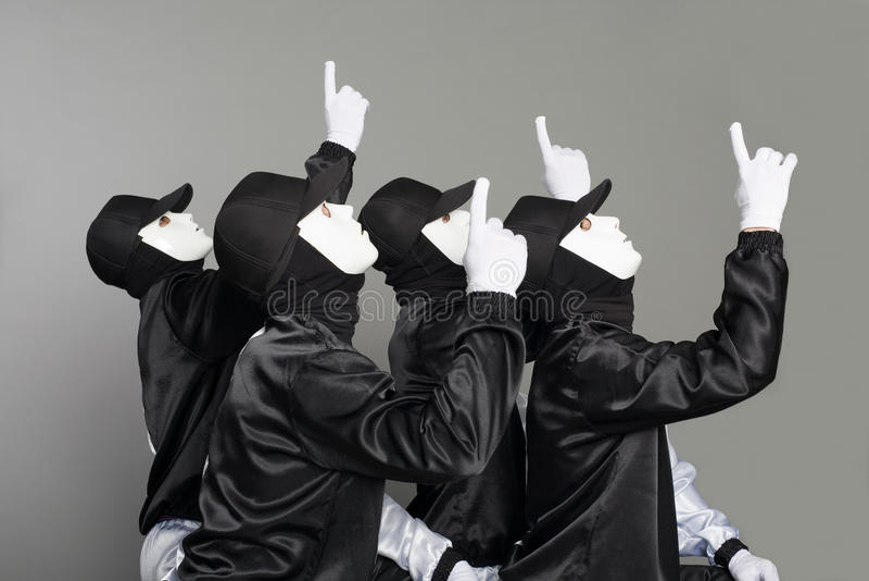 Squadra di giovani tiranti nelle mascherine che indicano in su immagini stock libere da diritti