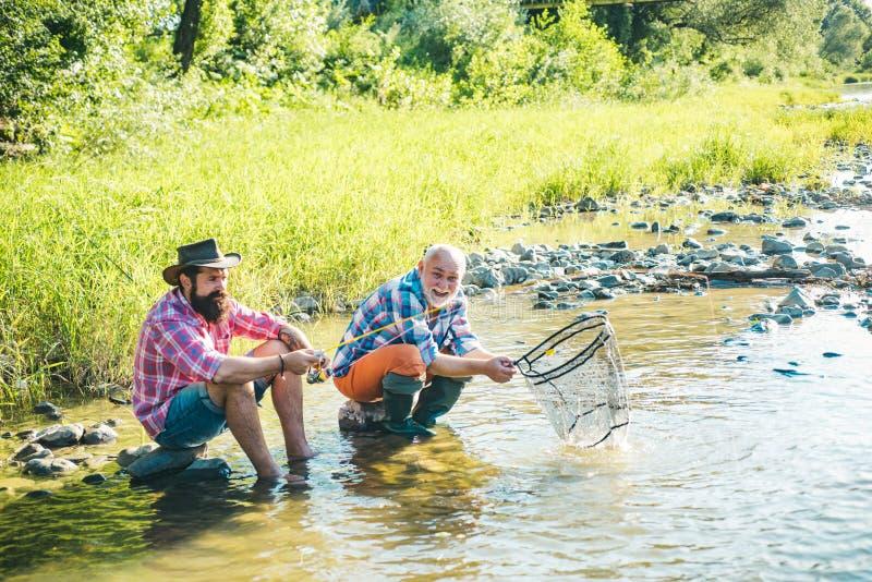 Squadra di pesca Brutali seduti vicino all'acqua del fiume Trasporto di pesca Divertiti e rilassati Angler che cattura il pesce A fotografie stock libere da diritti