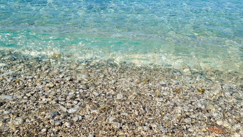 Square background image of calm turquoise sea on shingle beach.  stock photo