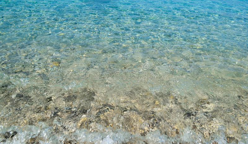 Square background image of calm turquoise sea on shingle beach.  royalty free stock photography