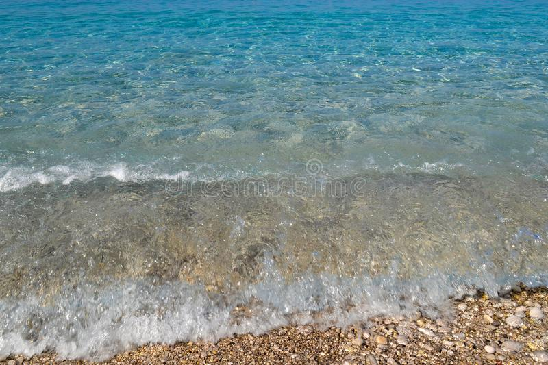 Square background image of calm turquoise sea on shingle beach.  royalty free stock photos