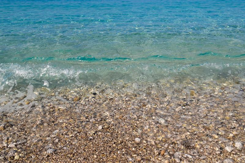 Square background image of calm turquoise sea on shingle beach.  royalty free stock images