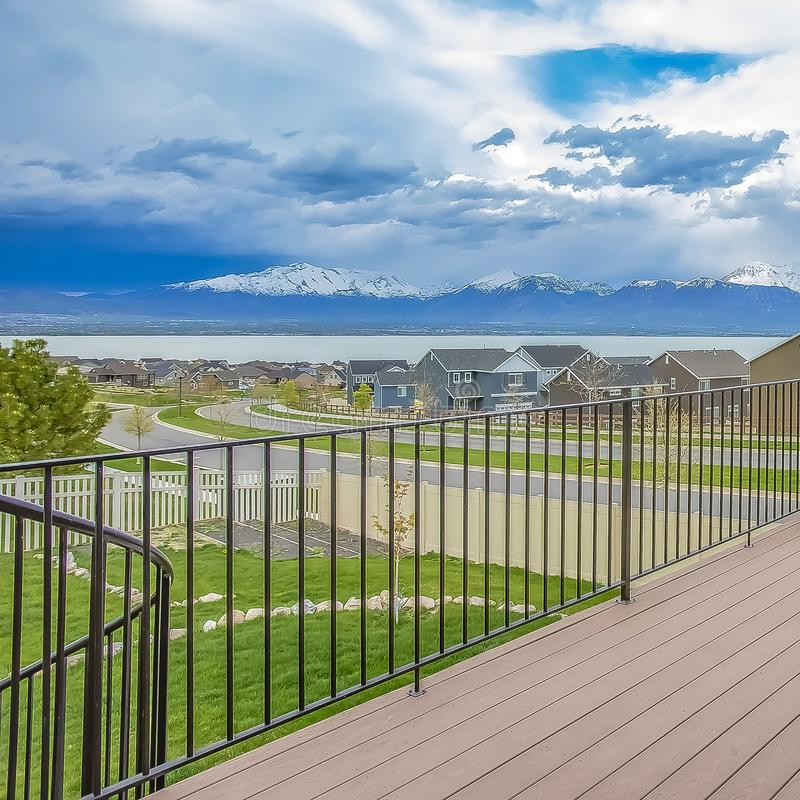 Square Balcony with wooden floor and metal railing overlooking lake and mountain. Houses along a curving road can also be seen under the striking cloudy blue stock photos