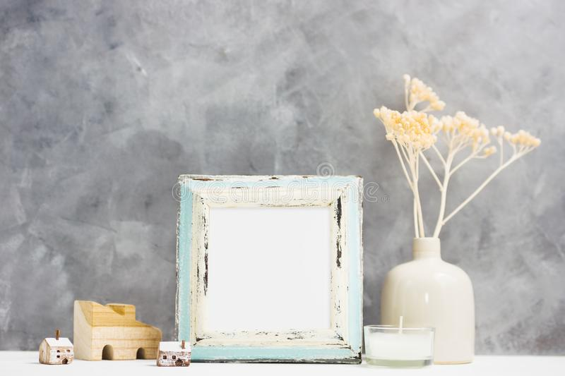 Square blue Photo frame mock up with dry beige plants in vase, wooden houses on shelf. Scandinavian style stock images