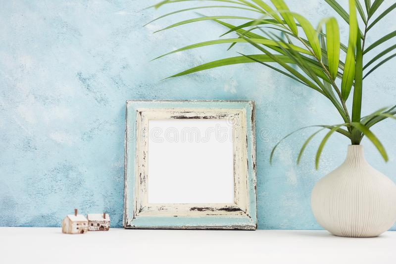 Square blue Photo frame mock up with green tropical plants in vaseand small wooden houses on shelf. Scandinavian style stock photography