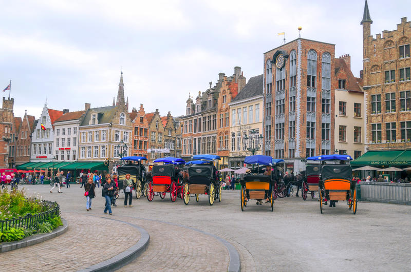Square of Bruges. Square with the statue of the medieval city of Bruges in Belgium with people walking on it, is an editorial image taken in September 2014 under stock photos