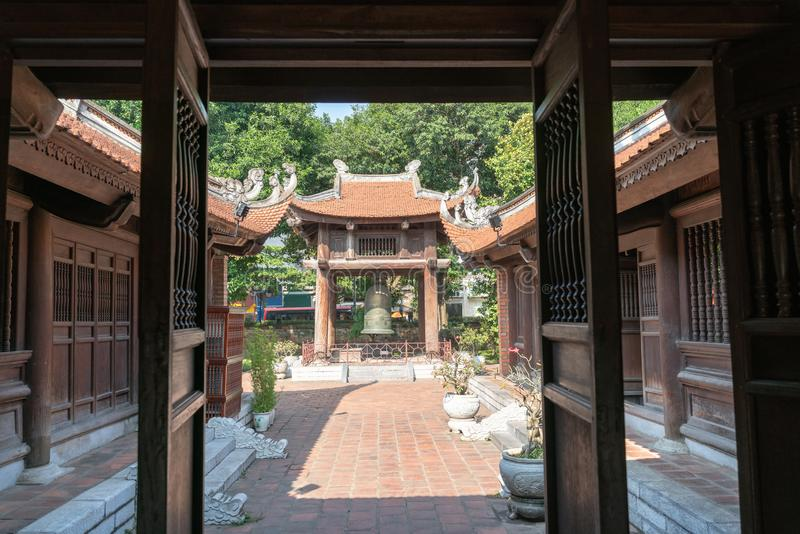 Square building holding a big bell on side of Imperial Academy in Temple of Literature Van Mieu, view inside out of main house stock images