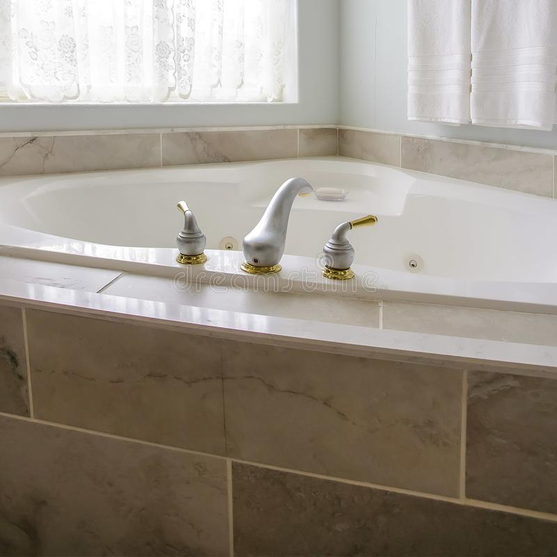 Square Built in bathtub at the corner of a bathroom with a large arched window stock photography