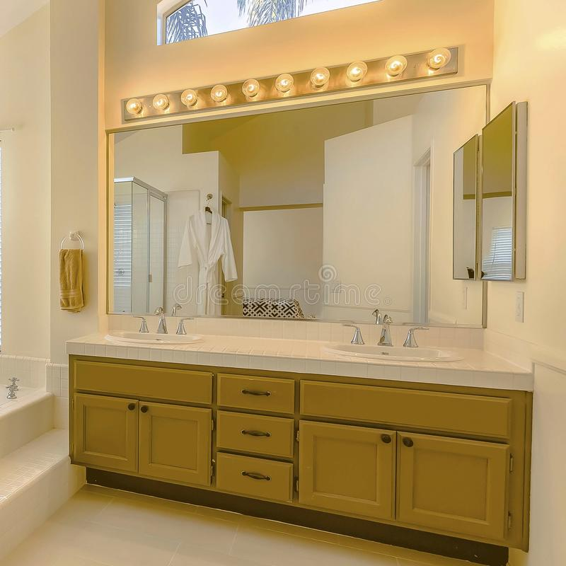 Square Built in bathtub and shower with glass door inside a beautiful bathroom. Vanity unit with double sink, large mirror, bright lights, and wood cabinets stock images