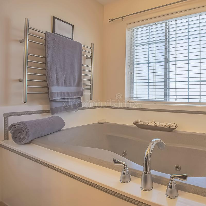 Square Built in bathtub and wall mounted towel rack inside a bathroom with beige wall. Bathroom ornaments and windows with blinds can also be seen inside this stock photo