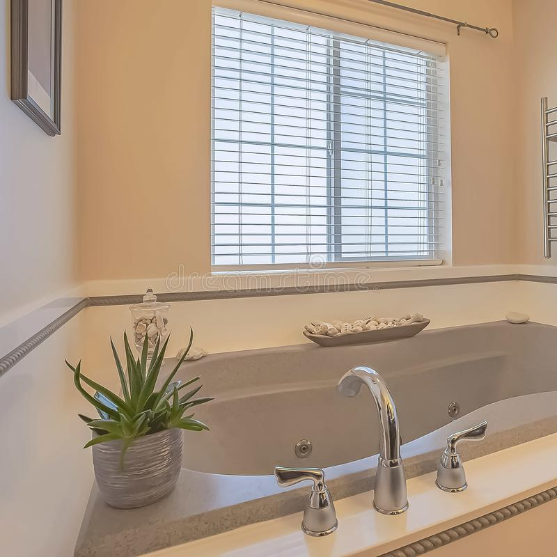 Square Built in bathtub and wall mounted towel rack inside a bathroom with beige wall. Bathroom ornaments and windows with blinds can also be seen inside this stock photos