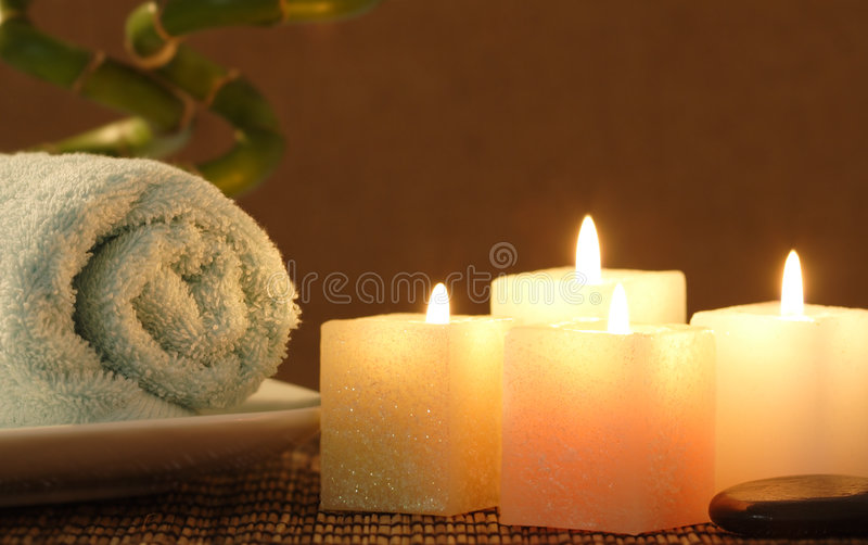 Square candle and towel before bamboo