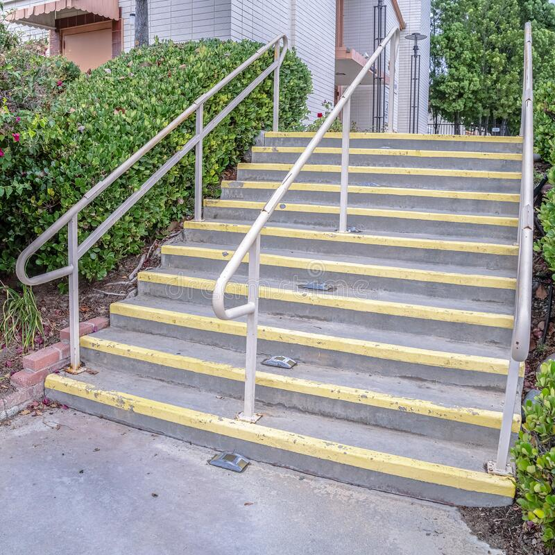 Square Cement entrance steps with yellow warning on a sunny day. Square Cement entrance steps with yellow warning painted on the treads viewed from below with royalty free stock photos