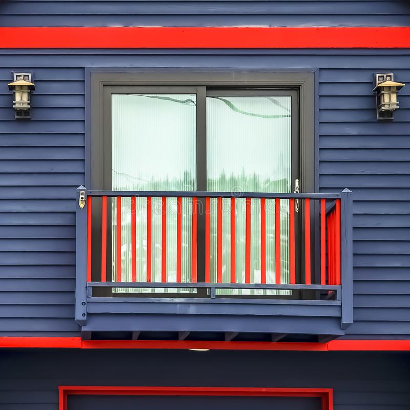 Square Close up of home exterior with vibrant blue wall red frames and small balcony. Cloudy sky and mountain covered with snow in winter cna be seen in the royalty free stock photography