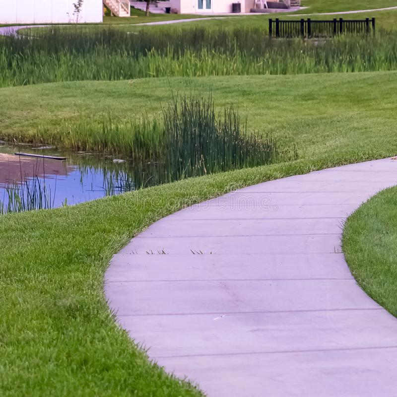 Square Close up of a pathway curving through a lush grassy terrain with a shiny pond. A short bridge and outdoor bench can be seen in the background stock photos