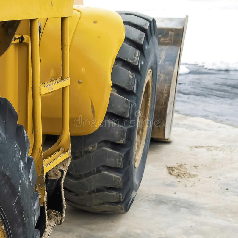 Square Close up view of the black rubber wheel of a yellow construction machinery. The heavy duty wheel has a dirty yellow rim with caked mud royalty free stock photo