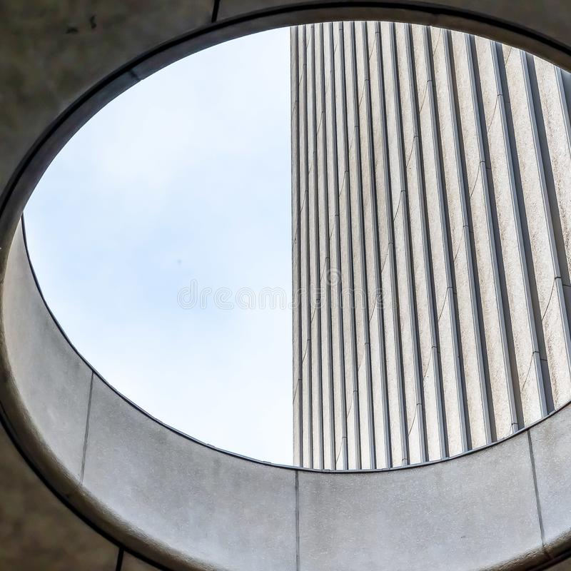 Square Close up view from the inside of the round skylight of a building. Corrugated concrete wall and bright sky can be seen through the hole stock photography
