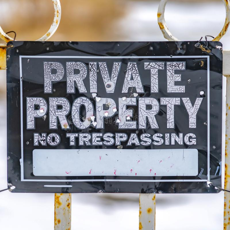 Square Close up view of a weathered sign that reads Private Property No Trespassing. The signage is hanging on a white metal gate damaged by rust stock photo