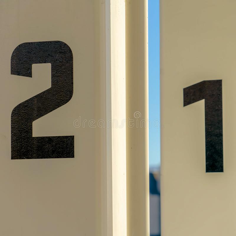 Square Close up of white rectangular posts with numbers painted on the surface. Building and sky cna be seen in the blurry backgroun on this sunny day royalty free stock images
