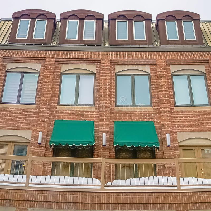 Square Cloudy sky and string lights over a building with brick wall and snowy balcony royalty free stock photos