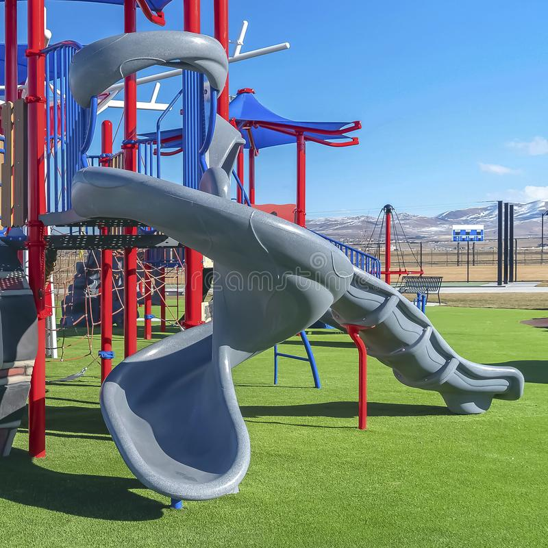 Square Colorful playground for children on a grassy terrain viewed on a sunny day. Snow capped mountain under bright blue sky can be seen in the distance stock photography
