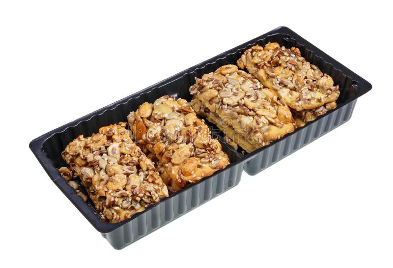 Square cookies crackers with raisin , nuts,  peanut  and seeds  in black plastic box  isolated royalty free stock image