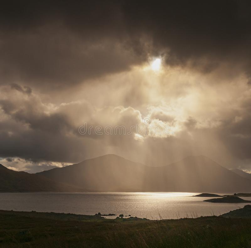 Square crepusculars. Looking Towards Sgurr Mor and Sgurr an Fhuarain across Loch Quoich through the rain and crepuscular rays stock photo