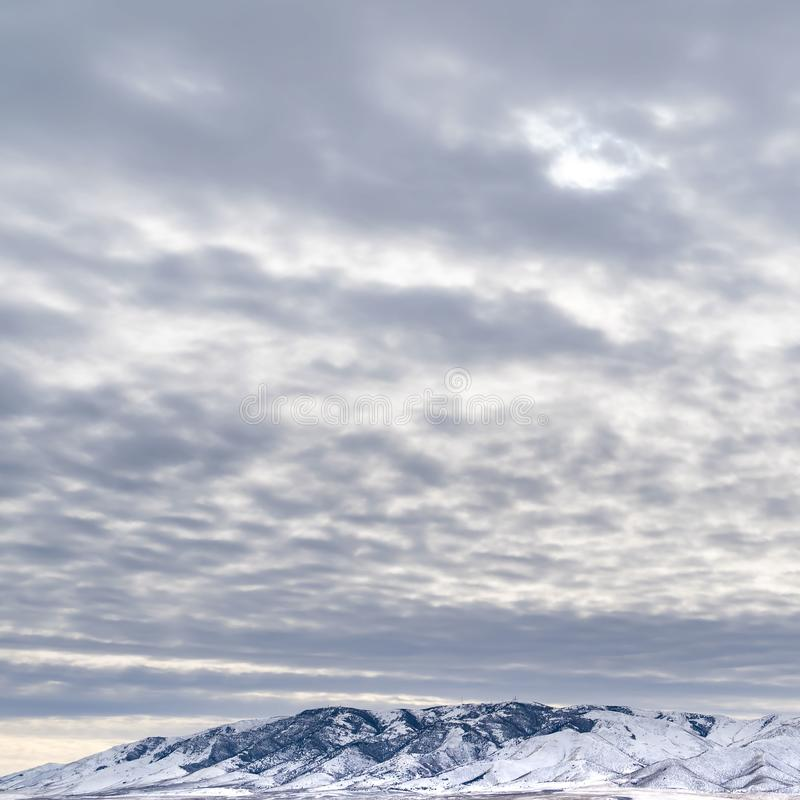 Square Dramatic sky filled with cottony clouds over a scenic landscape in winter. A lake and snow capped mountain cna be seen beyond the vast grassy terrain royalty free stock photos