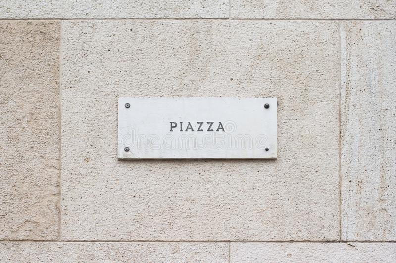Square empty marble plaque signboard on a building with classic. Horizontal closeup of square empty marble plaque signboard with the word piazza written on a stock image