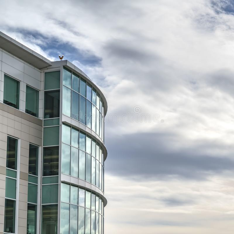 Square Exterior of a modern building with shiny and reflective glass windows. The blue sky filled with clouds in the background is mirrored on the glass royalty free stock image