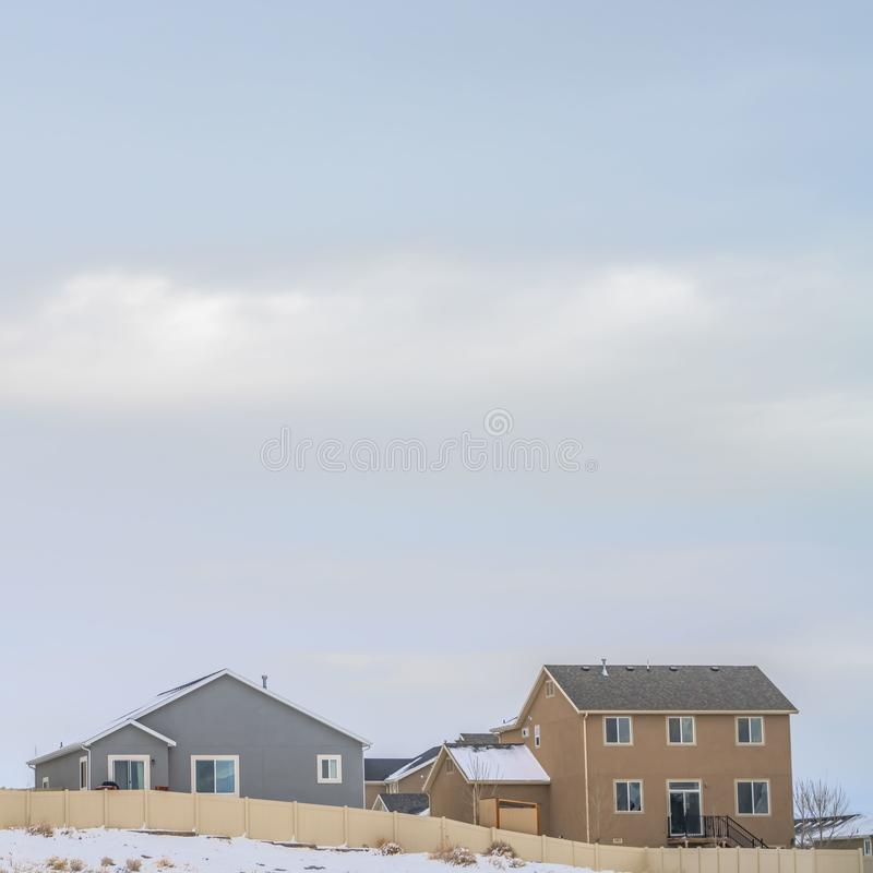 Square Facade of houses with a boundless cloudy sky background in winter. A terrain coated with fresh powdery snow cna be seen in front of the wooden fence royalty free stock photo