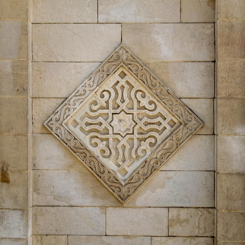 Square floral pattern unit carved into exterior stone wall of Al Hakim Mosque, Old Cairo, Egypt. Square floral pattern unit carved into the exterior ancient stock photography