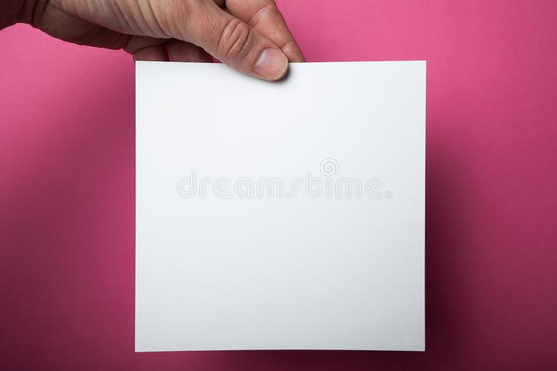 Square Flyer in male hands, holding a white paper blank on a pink background. Invitation Mock-Up stock images