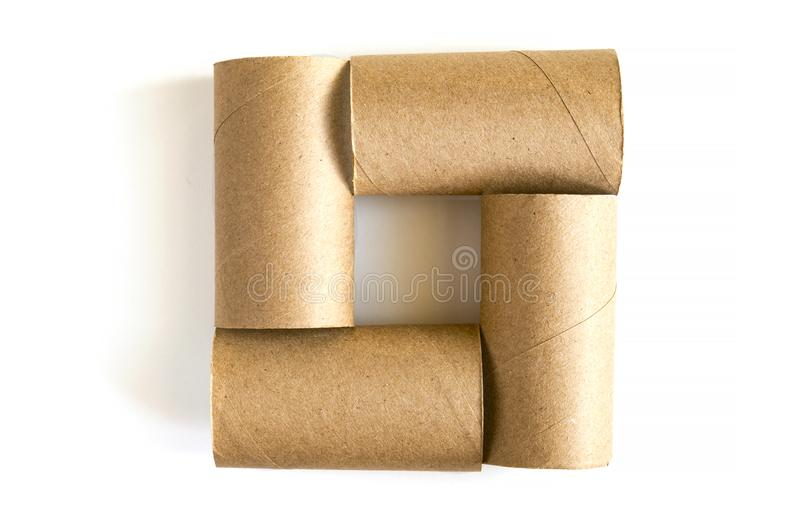 Square formed from of four cardboard paper tubes on white background. Close-up of empty toilet rolls, top view stock photo