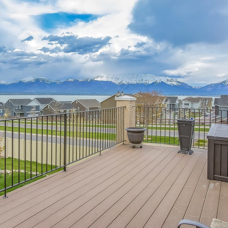 Square frame Balcony with wooden floor and metal railing overlooking lake and mountain. Houses along a curving road can also be seen under the striking cloudy stock photos