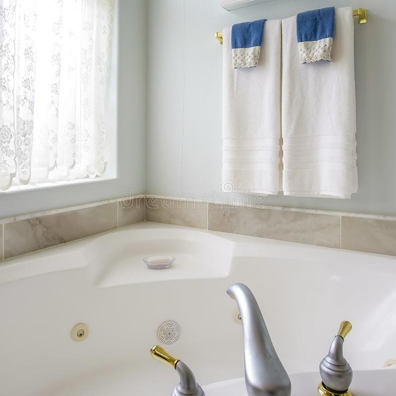 Square frame Bathroom interior with agleaming bathtub beside a large arched window royalty free stock photography