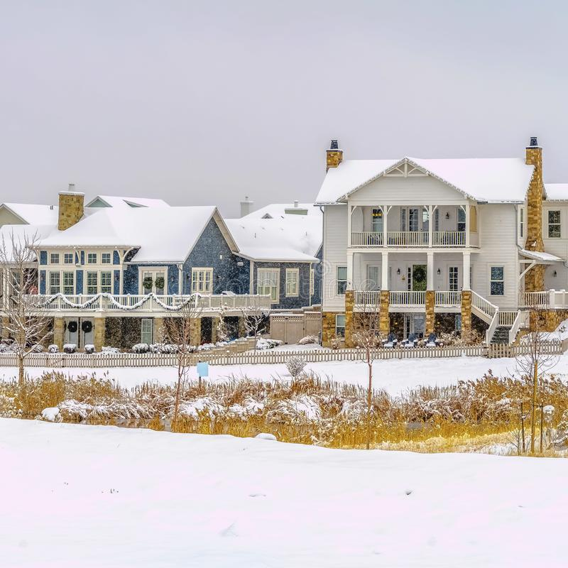 Square frame Beautiful houses in front of a silvery lake against cloudy sky in winter. The scenic landscape as well as the roof of the homes are covered with royalty free stock photos