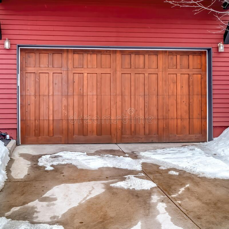 Free Square Frame Brown Garage Door And Red Wall Of Home With Snowy Yard And Driveway In Winter Stock Image - 186972911