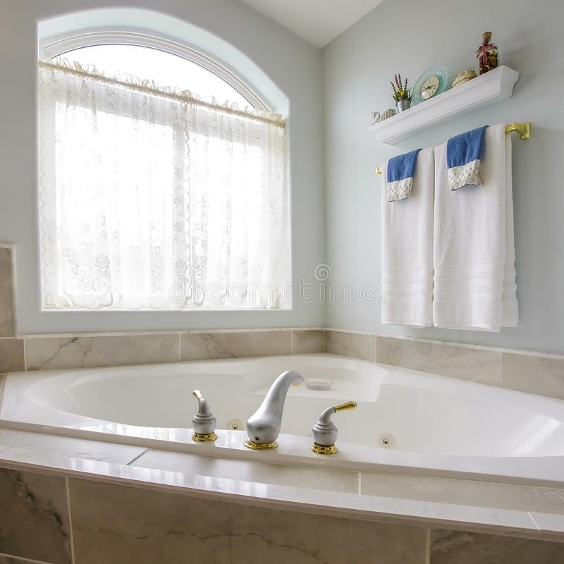 Square frame Built in bathtub at the corner of a bathroom with a large arched window royalty free stock images