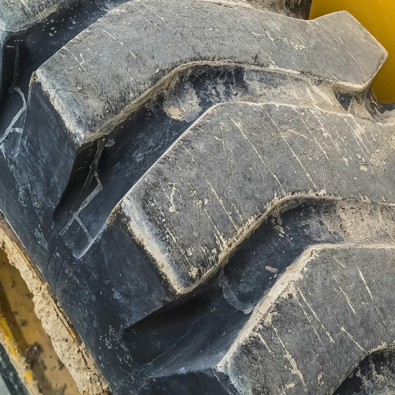Square frame Close up of the black rubber tire of a construction vehicle with yellow paint stock photos