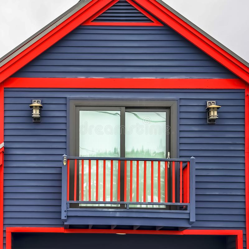 Square frame Close up of home exterior with vibrant blue wall red frames and small balcony. Cloudy sky and mountain covered with snow in winter cna be seen in royalty free stock photography