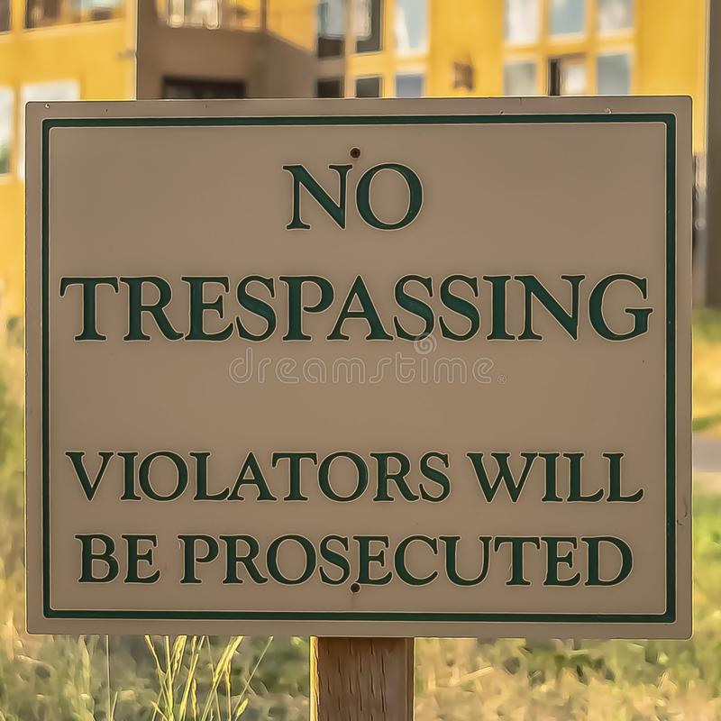 Square frame Close up of No Trespassing sign post beside a paved road that leads to houses stock photography