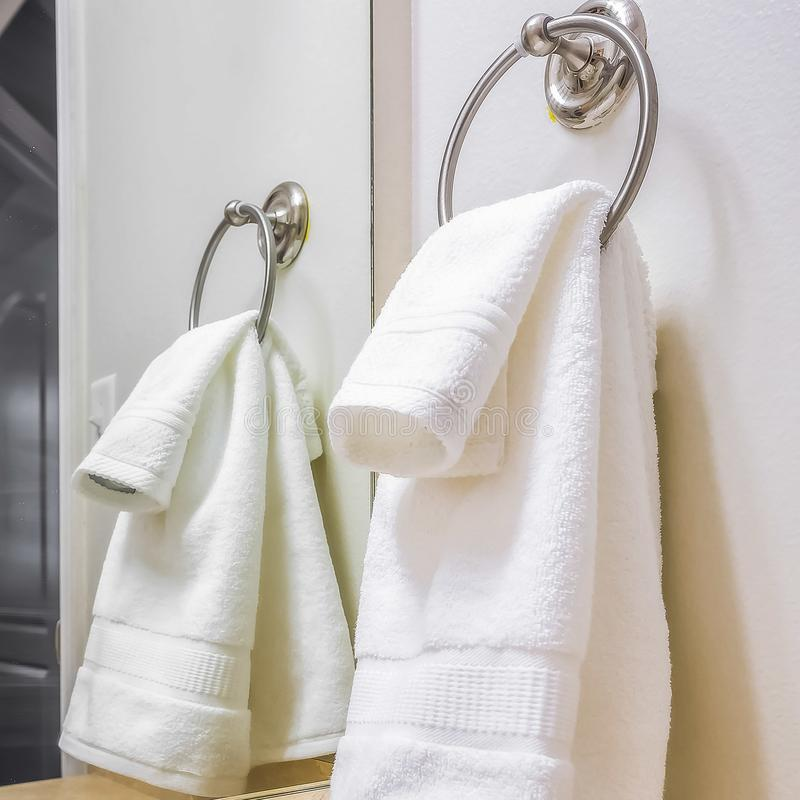 Square frame Close up of a white towel hanging on a metal ring mounted on the bathroom wall royalty free stock image